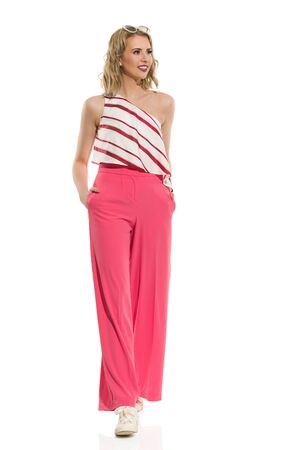 Fashion model in red wide leg trousers and striped top is walking towards camera and looking away. Full length studio shot isolated on white.