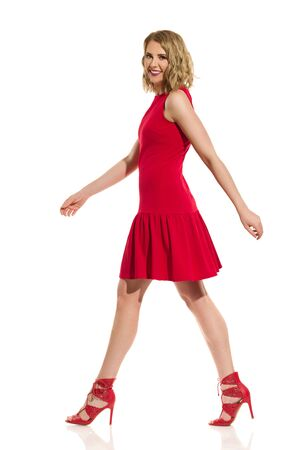 Beautiful young woman in red mini dress and high heels is walking, smiling and looking at camera. Full length studio shot isolated on white. Reklamní fotografie
