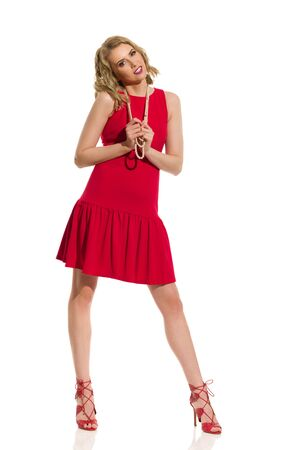 Beautiful young woman in red mini dress, pearl necklace and high heels is standing legs apart and looking at camera. Full length studio shot isolated on white.