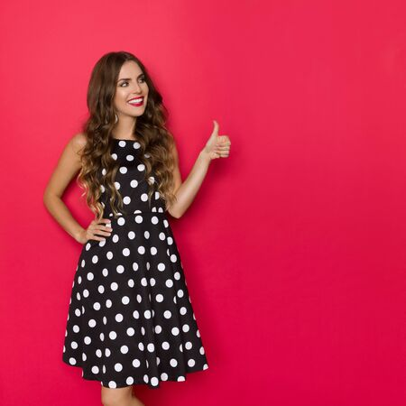Beautiful young woman in black cocktail dress in polka dots pattern is looking away, smiling and showing thumb up. Three quarter length studio shot on red background. Banco de Imagens