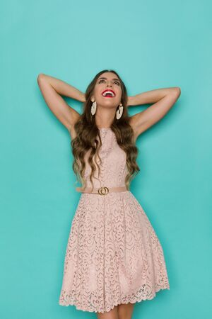 Excited beautiful young woman in beige lace mini dress is standing, holding hands behind head, looking up and laughing. Three quarter length studio shot on turquoise background.