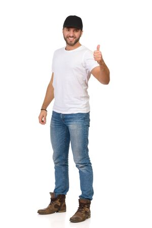 Handsome young man in jeans, white t-shirt and black cap is standing and showing thumb up. Full length studio shot isolated on white. Banco de Imagens