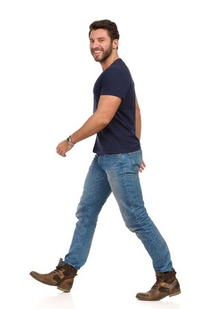 Smiling handsome man is walking in jeans, boots and blue t-shirt and looking at camera. Side view. Full length studio shot isolated on white. Standard-Bild
