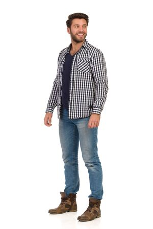 Handsome man is standing relalxed in unbuttoned lumberjack shirt and looking away over the shoulder. Full length studio shot isolated on white.