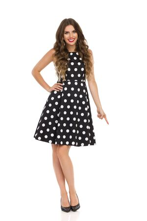 Happy beautiful young woman in black cocktail dress in polka dots and high heels is looking at camera, smiling and pointing down. Full length studio shot isolated on white.