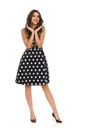 Beautiful young woman in black cocktail dress in polka dots and high heels is holding head in hands, looking at camera and smiling. Full length studio shot isolated on white.