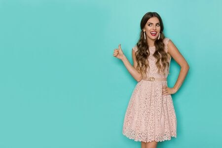 Happy beautiful young woman in beige lace mini dress is showing thumb up, looking away and talking. Three quarter length studio shot on turquoise background.