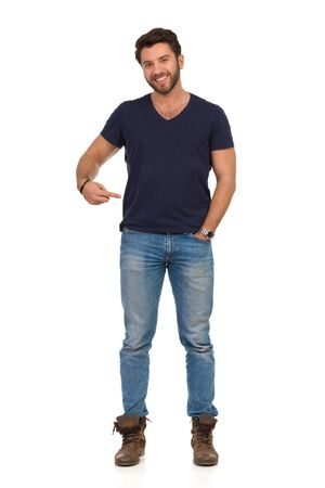 Handsome young man is pointing at his blue t-shirt, looking at camera and smiling. Full length studio shot isolated on white.