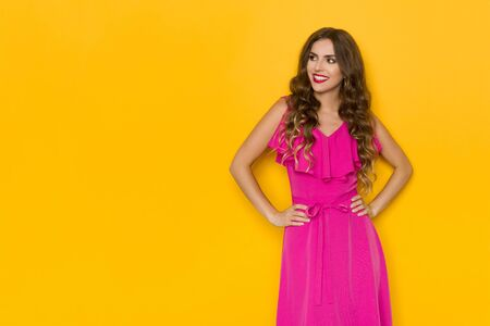 Beautiful young woman in pink dress is holding hands on hip, looking at the side and smiling. Three quarter length studio shot on yellow background.
