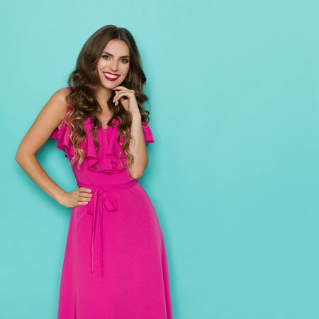 Beautiful young woman in elegant pink dress is holding hand on chin, looking at camera and smiling. Three quarter length studio shot on turquoise background.