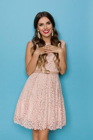 Beautiful young woman in beige lace mini dress is holding hands on chest, looking at camera and smiling. Three quarter length studio shot on blue background.