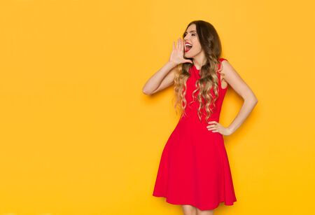 Happy young woman in red mini dress is holding hand on chin, looking away and shouting. Three quarter length studio shot on yellow background.