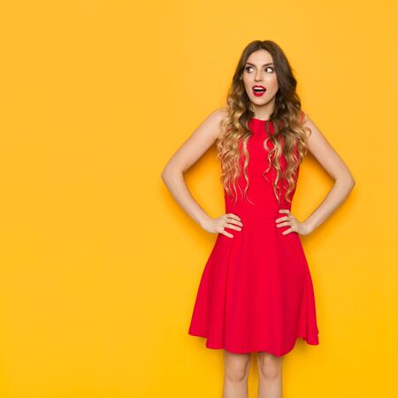 Surprised beautiful young woman in red mini dress is holding hands on hip and looking away. Three quarter length studio shot on yellow background. Imagens