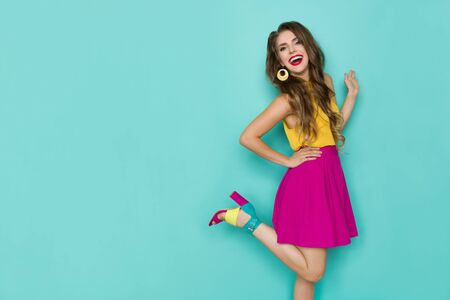 Beautiful young woman in vibrant clothes and high heels is standing on one leg, laughing and looking at camera. Three quarter length studio shot on turquoise background.