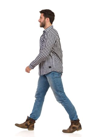 Smiling man is walking in boots, jeans and lumberjack shirt and looking away. Side view. Full length studio shot isolated on white. Banco de Imagens