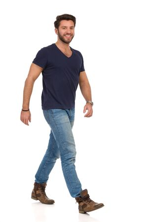 Happy man is walking in jeans, boots and blue t-shirt and looking at camera. Full length studio shot isolated on white. Banco de Imagens
