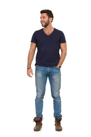 Handsome man in jeans and blue t-shirt is standing with hand in pocket, looking away and smiling. Front view. Full length studio shot isolated on white. Banco de Imagens