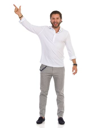Handsome man in gray trousers and white shirt is standing, pointing up and talking. Full length studio shot isolated on white. Banco de Imagens