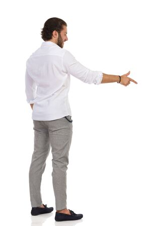 Handsome man in gray trousers and white shirt is standing, aiming with his index finger and looking away. Side view. Full length studio shot isolated on white. Banco de Imagens