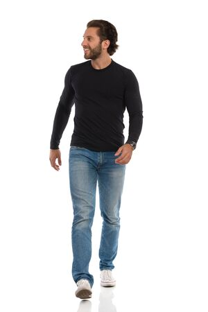 Smiling young man in jeans, sneakers and black jersey is walking towards camera and looking away. Full length studio shot isolated on white.