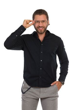 Smiling young man in black shirt is holding eyeglasses and looking at camera. Three quarter length studio shot isolated on white.