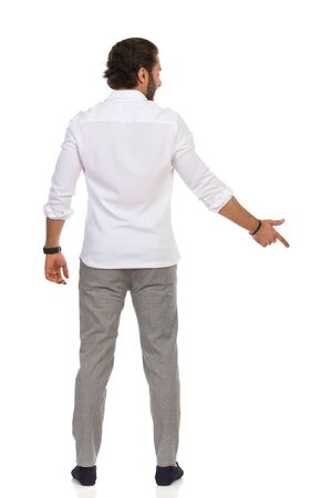 Handsome man in gray trousers and white shirt is standing and pointing down. Rear view. Full length studio shot isolated on white.