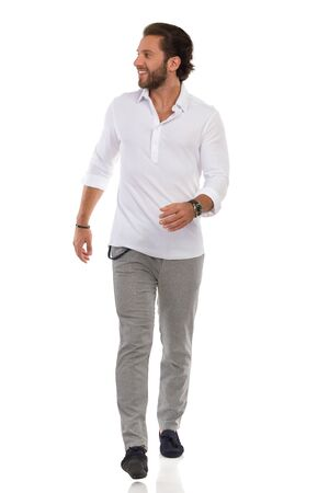Smiling young man in moccasins, gray trusers, and white shirt is walking towards camera and looking away. Full length studio shot isolated on white.