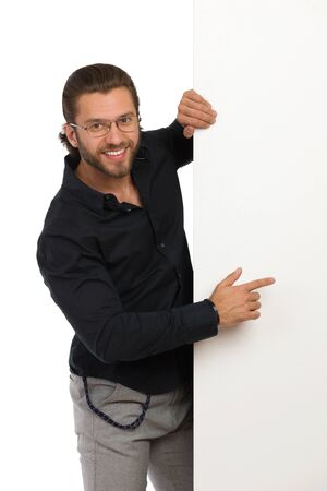 Smiling young man in black shirt and eyeglasses is standing next to big banner and pointing at it. Three quarter length studio shot isolated on white.
