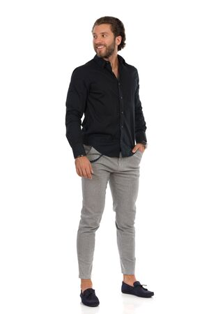 Handsome man in moccasins, gray trousers and black shirt is standing, holding hand in pocket and looking away. Full length studio shot isolated on white.
