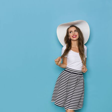 Beautiful young woman in striped mini skirt, white top and big sun hat is looking away at copy space and smiling. Three quarter length studio shot on blue background.