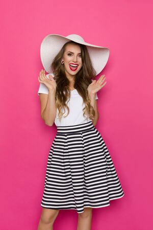 Excited beautiful young woman in striped mini skirt, white top and big sun hat is holding hands raised and shouting. Three quarter length studio shot on pink background.