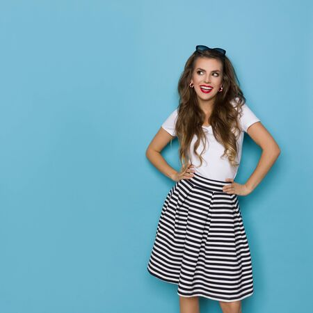 Happy young woman in striped mini skirt and white top is holding hands on hip, looking away and talking. Three quarter length studio shot on blue background. Banco de Imagens