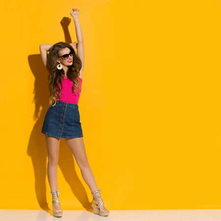 Beautiful young woman in jeans mini skirt, magenta top and wedges is standing with arm raised, looking away and smiling. Full length studio shot on yellow background. Banco de Imagens