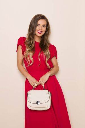 Beautiful young woman in red dress is holding beige purse, looking at camera and smiling. Three quarter length studio shot on beige background.