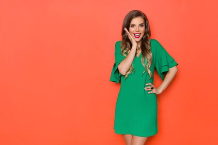 Surprised beautiful young woman in green mini dress is holding hand on chin, looking at camera and shouting. Three quarter length studio shot on orange background.