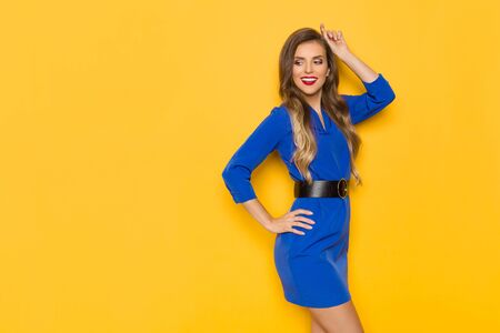 Beautiful young woman in blue mini dress is posing and  looking away over shoulder. Three quarter length studio shot on yellow background.