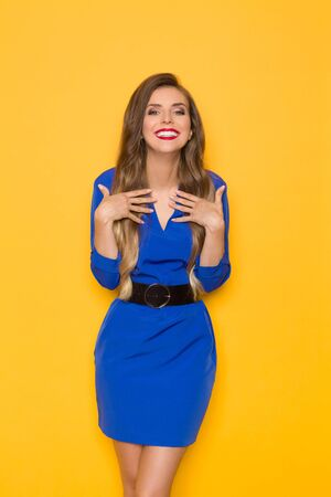 Beautiful young woman in blue mini dress is posing with hands on chest, looking at camera and smiling. Three quarter length studio shot on yellow background.