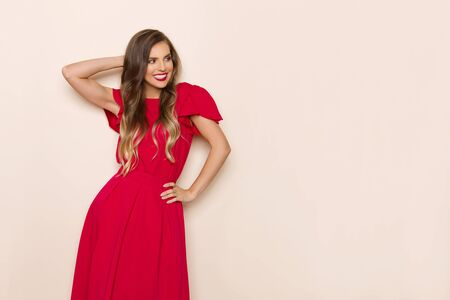 Beautiful young woman in red dress is holding hand behind head, looking away and smiling. Three quarter length studio shot on beige background.