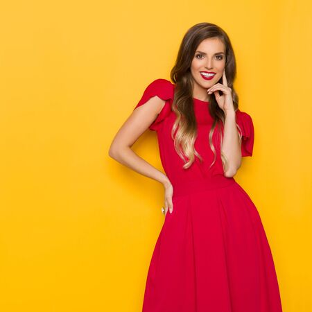 Beautiful elegant woman in red dress is holding hand on chin, looking at camera and smiling. Three quarter length studio shot on yellow background.