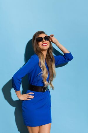Beautiful young woman in blue mini dress and sunglasses is smiling in the sunlight. Three quarter length studio shot on blue background.