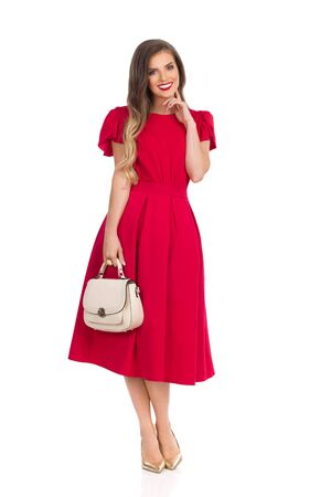 Elegant young woman in red dress and gold high heels is holding beige purse, looking at camera and smiling. Full length studio shot isolated on white.
