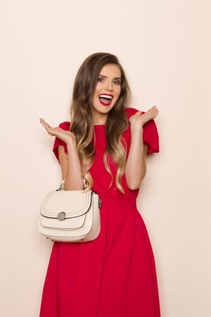 Beautiful young woman in red dress and beige purse is holding hands raised and laughing. Three quarter length studio shot on beige background.