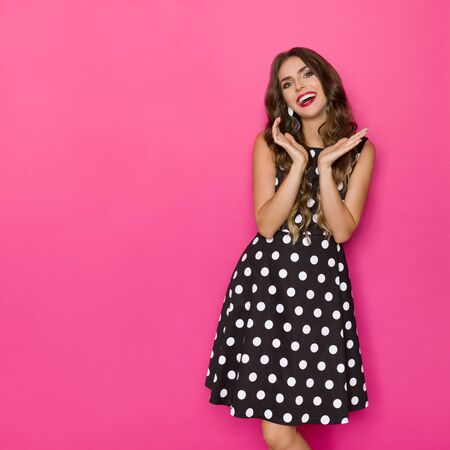 Smiling beautiful young woman in black cocktail dress in polka dots pattern is holding head in hands. Three quarter length studio shot on pink background.