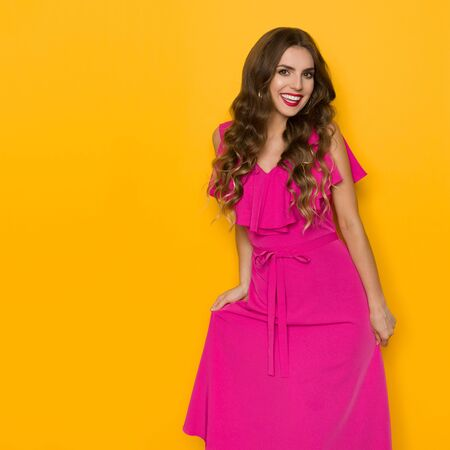 Beautiful young woman is presenting her pink dress and smiling. Three quarter length studio shot on yellow background.
