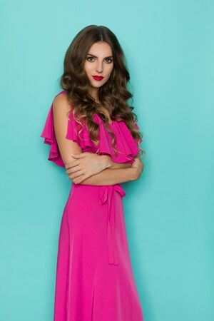 Beautiful young woman in elegant pink dress is posing with arms crossed and looking at camera. Three quarter length studio shot on turquoise background.