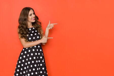 Smiling beautiful young woman in elegant black cocktail dress in polka dots pattern is looking away and pointing. Three quarter length studio shot on orange background.