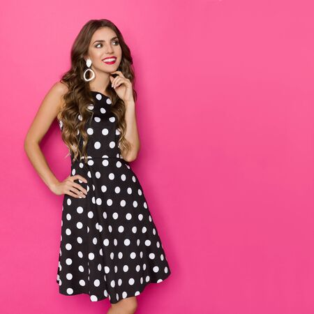 Smiling elegant young woman in black cocktail dress in polka dots pattern is holding hand on chin and looking at copy space. Three quarter length studio shot on pink background.