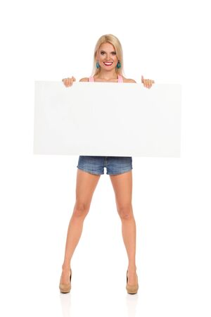 Young woman is standing legs apart, showing white poster and looking at camera. Front view. Full length studio shot isolated on white.