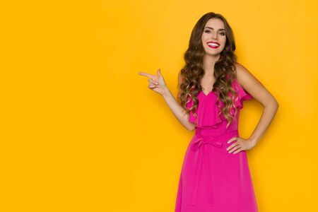 Beautiful smiling young woman in elegant pink dress is pointing at copy space and looking at camera. Three quarter length studio shot on yellow background. Banco de Imagens