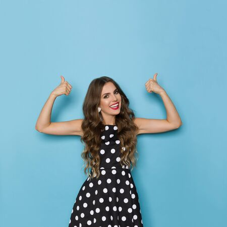 Beautiful young woman in black cocktail dress in polka dots pattern is looking at camera, smiling and pointing with thumbs up. Three quarter length studio shot on blue background. Standard-Bild